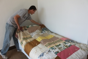 Ryan puts a handmade donated quilt on a client's new bed.