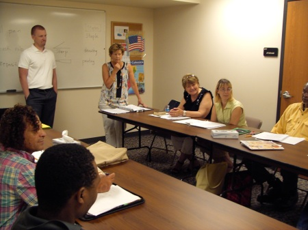 Eric Pauli, Xcel Energy Representative, visits with learners from the Introduction to Patient Care Course taught by English Instructor and former nurse, Carol Hudson.