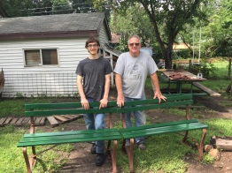 Mentor and his student standing by a bench they built together.